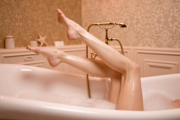 Donna in bagno con schiuma che mostra le gambe