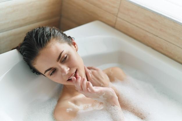 La donna fa il bagno in una vasca da bagno con il modello di capelli bagnati di acqua trasparente di schiuma bianca