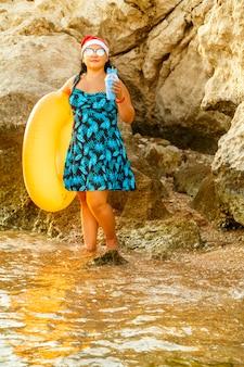 Una donna in costume da bagno e cappello di babbo natale in riva al mare vicino agli scogli con