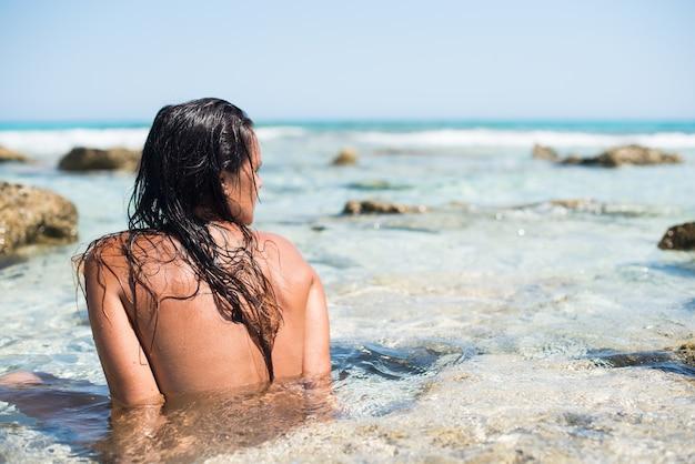 Donna che fa il bagno in un mare paradisiaco di acque turchesi. con le spalle alla telecamera, guardando l'orizzonte. colpo a metà. isola di formentera. spagna.