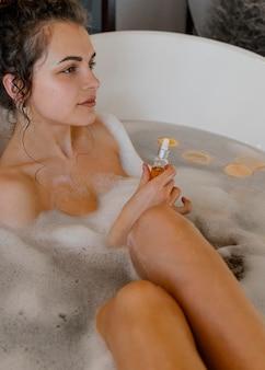 Donna che bagna con fette d'arancia in bagno
