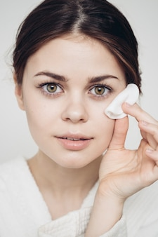 La donna in un accappatoio si pulisce il viso con una morbida spugna cosmetologica per la pelle pulita