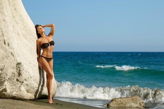 Donna sulla spiaggia accanto a scogliere bianche
