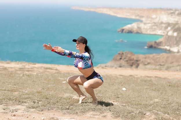 Donna sulla spiaggia facendo sport e facendo riscaldamento sulla costa del mare