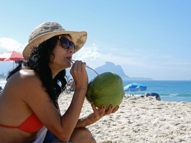 Donna sulla spiaggia che beve acqua di cocco a rio de janeiro