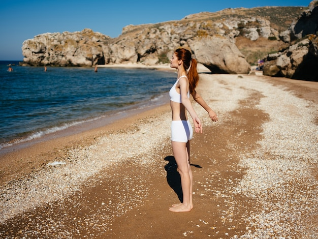 Donna sulla spiaggia costume da bagno bianco paesaggio vacanza ai tropici