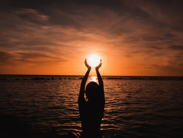 Donna su una spiaggia con le mani alzate