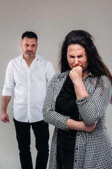 Una donna picchiata dal marito in piedi dietro di lei che la guardava aggressivamente. violenza domestica.
