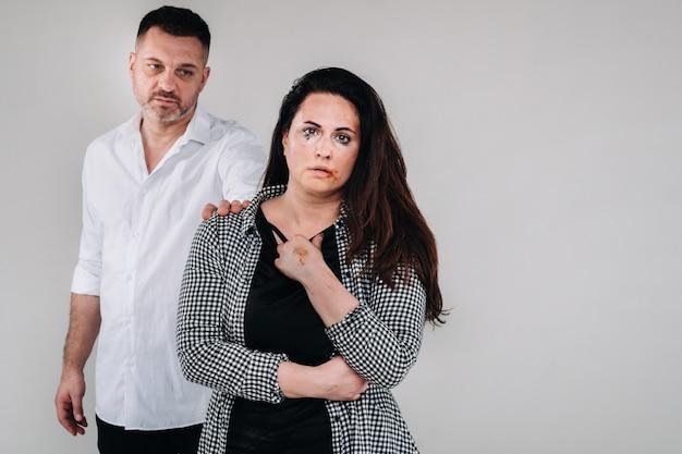 Una donna picchiata dal marito in piedi dietro di lei e la guarda in modo aggressivo