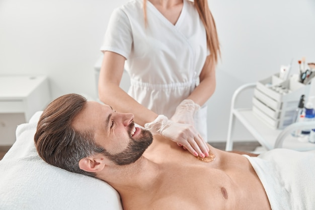L'estetista della donna ha messo la cera depilatoria al petto del giovane per la rimozione dei capelli. depilazione con cera.