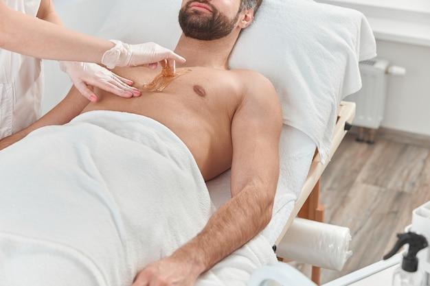 Estetista donna mettere cera depilatoria al petto del giovane per la depilazione. depilazione con cera.