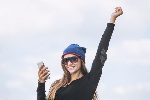 La bella modella della donna con il telefono contro il cielo fa il selfie