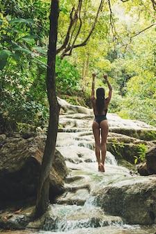 Donna sulla bellissima cascata nelle giungle