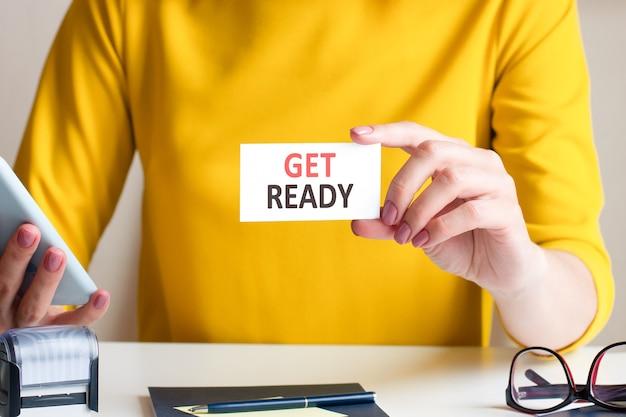 Una donna con un bel vestito giallo si siede alla scrivania di un ufficio e tiene davanti a sé un cartellino bianco con la scritta