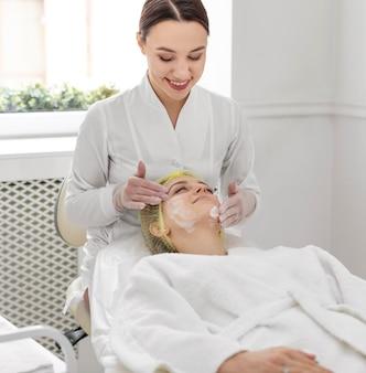Donna alla clinica di bellezza per il trattamento del viso