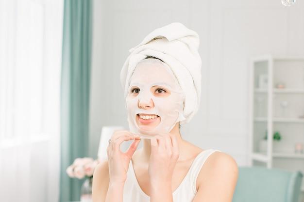 Volto di bellezza donna. primo piano di giovane femmina sorridente con trucco naturale fresco che applica la maschera facciale dello strato del tessuto. ritratto di attraente ragazza felice con maschera cosmetica bianca.