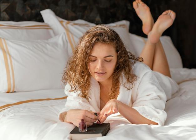 Donna a letto l'applicazione di smalto per unghie