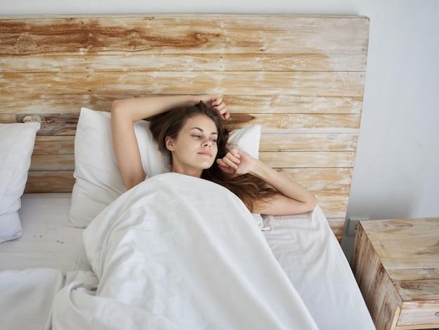 La donna a letto sotto le coperte riposa il sorriso mattina