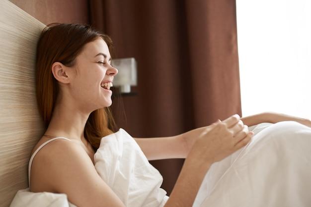 La donna a letto sotto le coperte si è svegliata al mattino presto vista ritagliata del modello