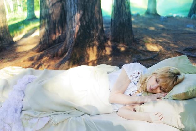 Donna in un letto nella foresta