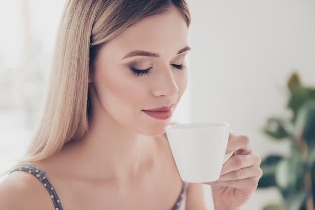 Donna a letto a casa a bere il caffè
