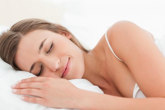 Donna a letto, dormendo e sorridendo dolcemente