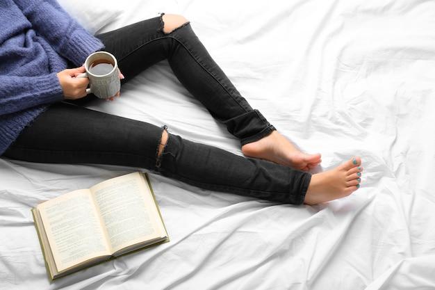 Donna sul letto con un vecchio libro e una tazza di caffè, punto di vista dall'alto