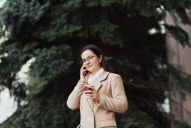 Donna in cappotto beige sta usando smartphone e tenendo la tazza di caffè di carta mentre si trovava all'aperto