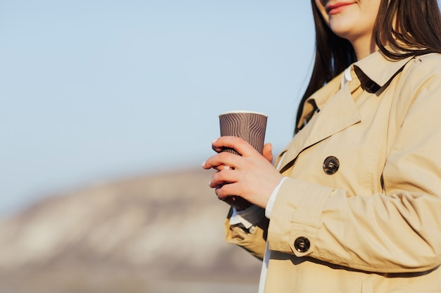 Donna in un cappotto beige con un bicchiere di carta tra le mani