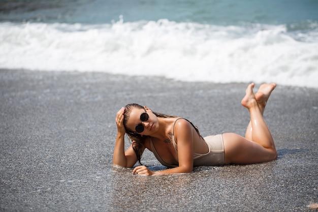 La donna in costume da bagno beige si trova su una spiaggia sabbiosa vuota vicino all'oceano