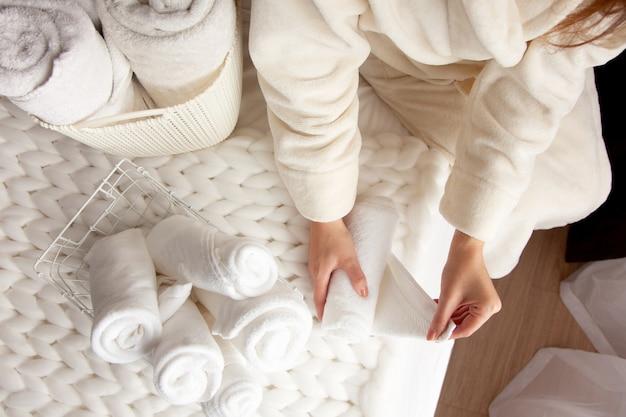 La donna in una calda veste beige sta piegando gli asciugamani bianchi puliti e mettendoli in un cesto di rete metallica su sfondo nero. copia spazio su sfondo nero. concetto di pulizia e organizzazione.