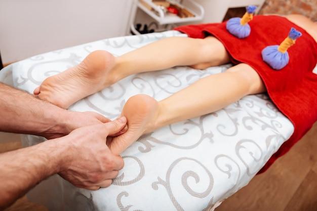 La donna è coperta. massaggiatore professionista nel salone spa che preme su punti speciali sui piedi durante il massaggio concentrato