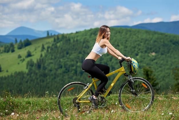 Donna ciclista in bicicletta bicicletta in montagna
