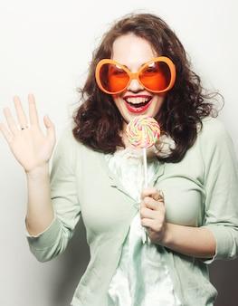 Donna in grandi occhiali arancioni leccare lecca-lecca con la lingua