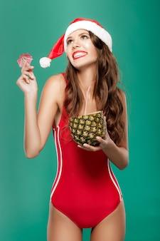 La donna in bikini beve un cocktail estivo all'ananas