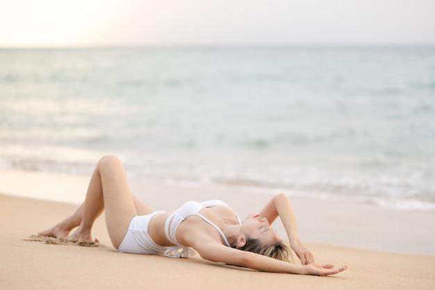 Donna in bikini sdraiata sulla spiaggia di sabbia rilassante per prendere il sole.