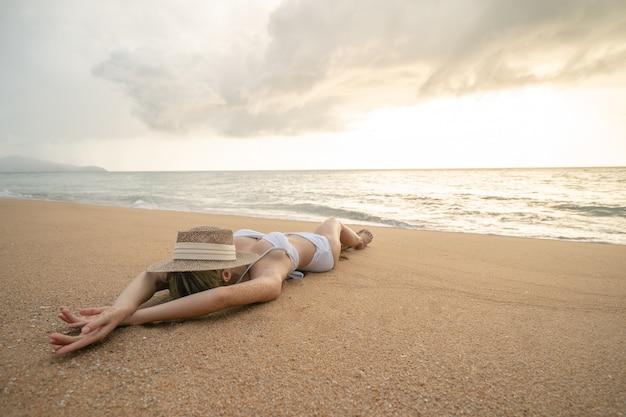 Donna in bikini sdraiata sulla spiaggia di sabbia con cappello di paglia che si copre il viso, rilassandosi prendendo il sole.