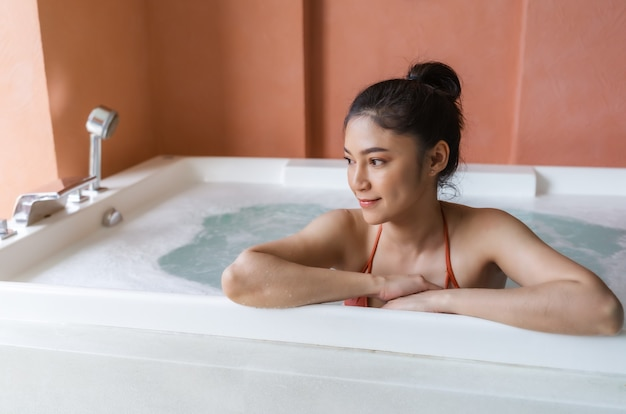 Donna in bikini rilassante all'interno di una vasca da bagno