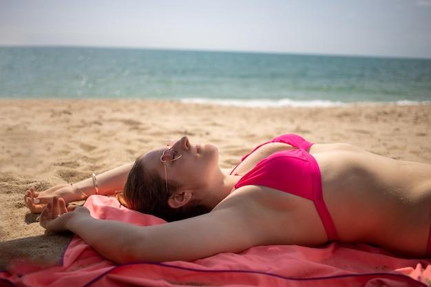 La donna in bikini prende il sole su una spiaggia assolata sullo sfondo del mare