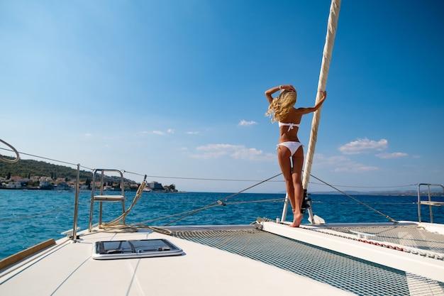 Donna in bikini che si abbronza e si rilassa durante una crociera estiva in catamarano