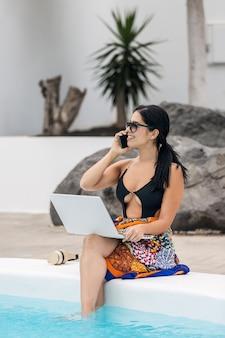 Donna in bikini in vacanza seduta a bordo piscina con computer e cellulare telelavoro