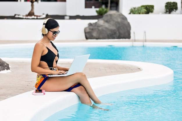Donna in bikini in vacanza seduta sul bordo della piscina con le cuffie che guarda un film sul suo computer portatile