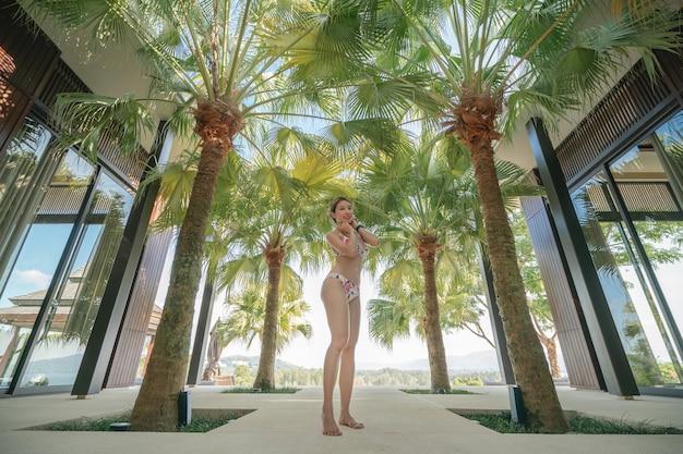 Donna in bikini che cammina verso la piscina, direzione con palme, cammina dalla villa all'acqua. vacanza