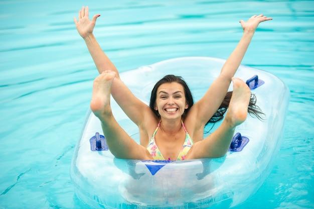 Una donna in bikini con un cerchio gonfiabile di gomma che gioca e si diverte nella piscina del parco di divertimenti in estate