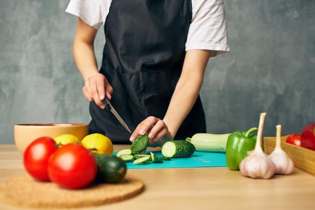 Donna in grembiule nero cottura del tagliere di alimentazione sana. foto di alta qualità