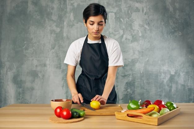Donna in grembiule nero che cucina un tagliere di alimentazione sana