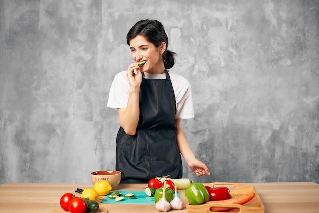 Donna in grembiule nero che cucina dieta sana