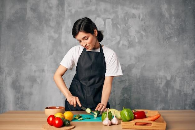 Donna in grembiule nero che cucina insalata di alimentazione sana