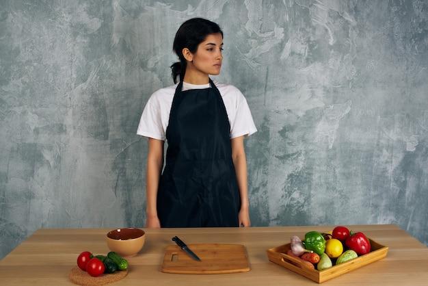 Donna in grembiule nero che cucina mangiando sano