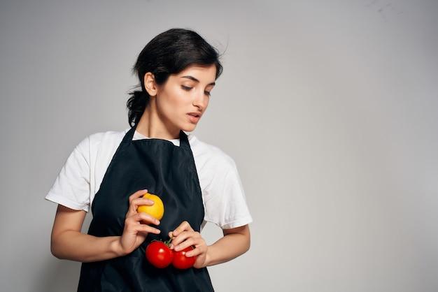 Donna in grembiule nero verdure fresche cibo sano